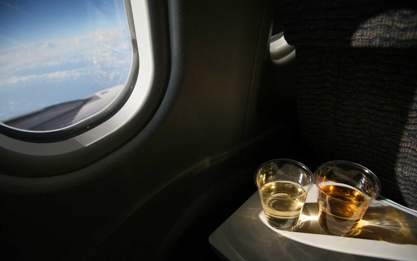 Two glasses of wine in aeroplane by window